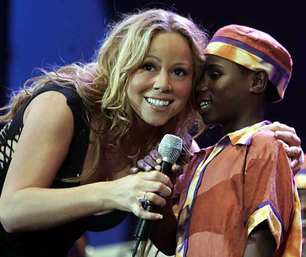 Mariah Carey and a member of an African choir perform at the Live 8 concert in Hyde Park, London, Saturday July 2, 2005. The concert is part of a series of free concerts being held around the world designed to press leaders of the rich G8 countries to help impoverished African nations. (AP Photo/Lefteris Pitarakis)