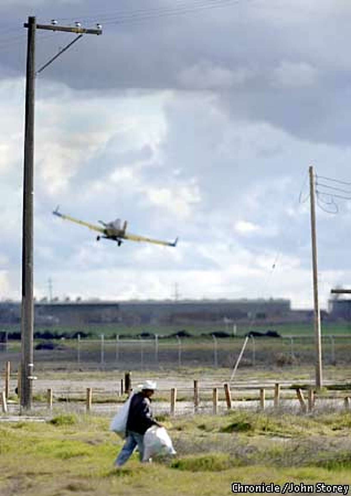 FIREBAUGH-C-13FEB03-MN-JRS-Story about the town of Firebaugh in the Central Valley for the Rural Poverty Series. A man walks with bags as a crop duster takes off in the background in Firebaugh. Chronicle photo by John Storey.
