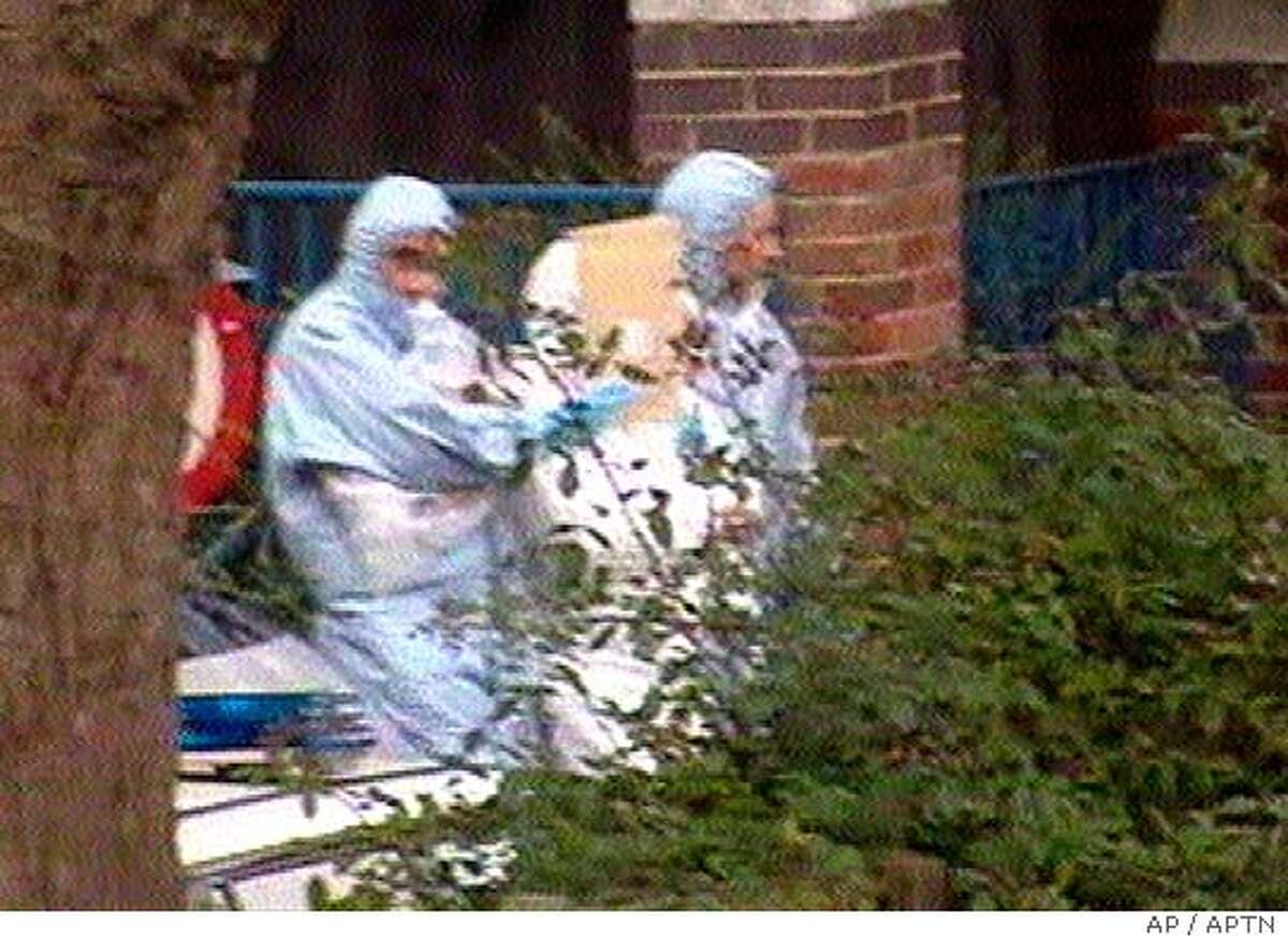 Police officers dressed in white overalls cover the face of a suspect, centre, as he is led from an apartment building in the Notting Hill area of London, Friday July 29, 2005, in this image made from television. Heavily armed police wearing gas masks and reportedly using stun grenades raided the apartment block seeking suspects in the failed July 21 attacks on London's transport system.(AP Photo/APTN) ** UNITED KINGDOM OUT: TV OUT **