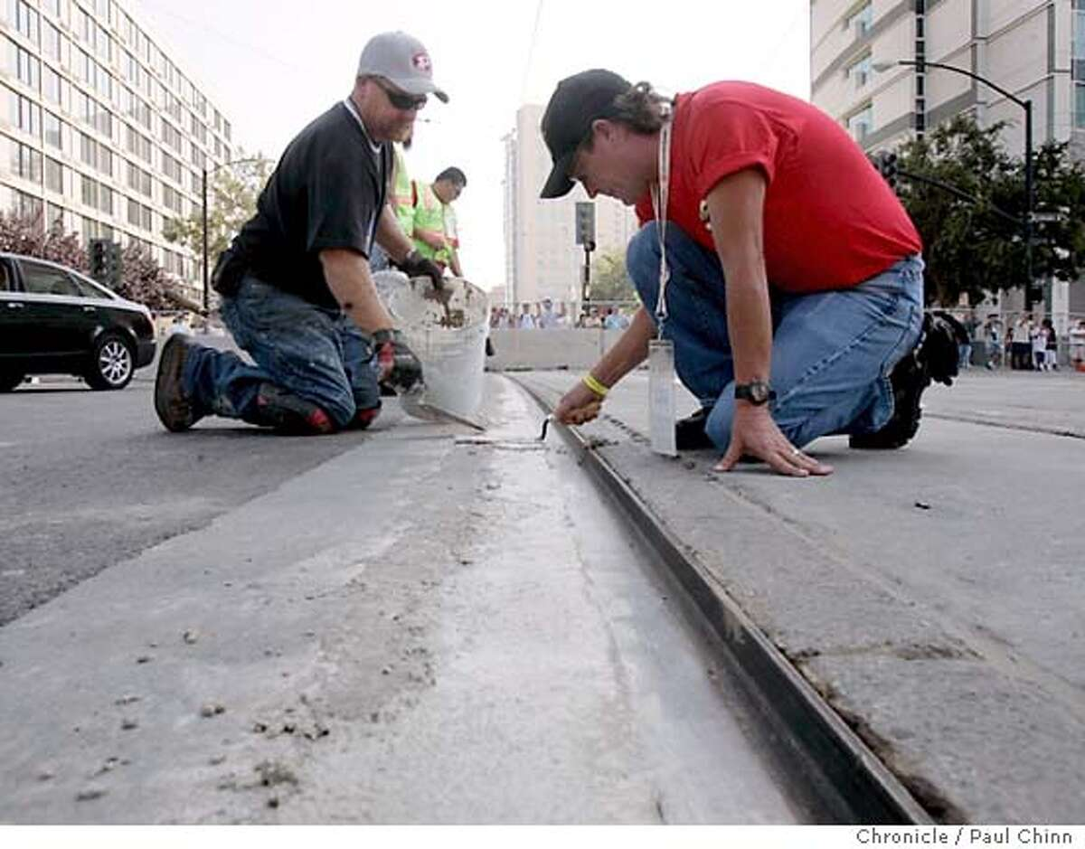 Road crews were still patching gaps along the light rail tracks crossing the race course which delayed Friday's preliminary events for several hours. Practice and qualifying sessions for the inaugural San Jose Grand Prix Champ Car racing series on 7/29/05 in San Jose, Calif. PAUL CHINN/The Chronicle