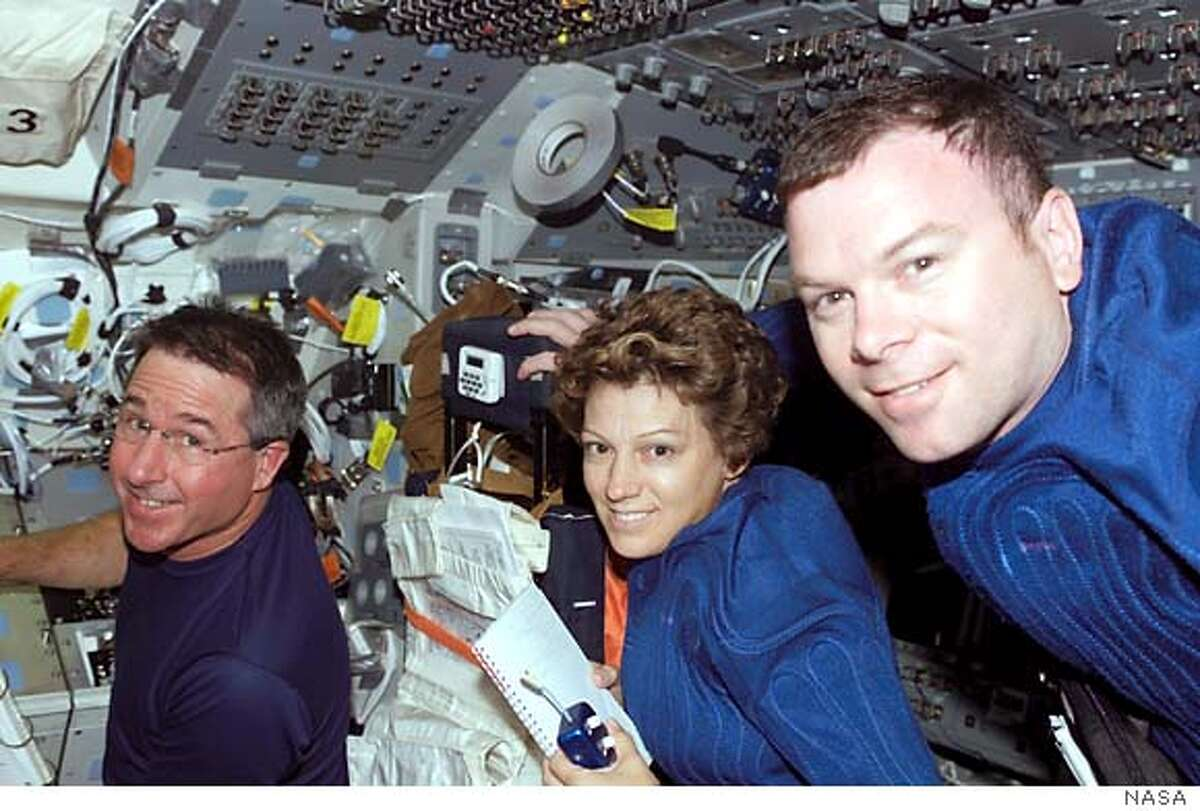 In this photo provided by NASA, space shuttle Discovery astronauts Eileen M. Collins, mission commander, and astronauts Stephen K. Robinson, left, mission specialist, and James M. Kelly, pilot smile while another crew member snaps the photo. (AP Photo/NASA)