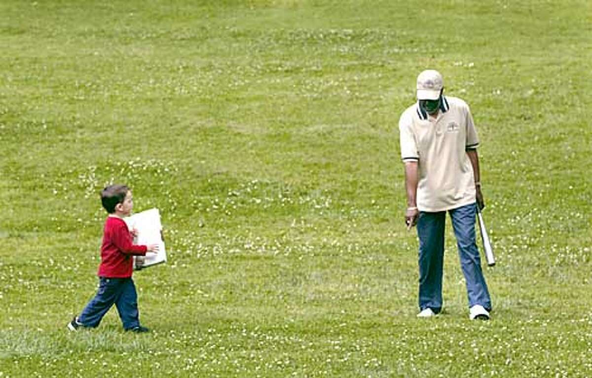 the coach of the team Birrel (CQ) Nicholson, who has been running the program at Dimond Rec Center for 11 years, shows Dillon Scanlin, 3 1/2, where the base goes. Tot T-Ball at the Dimond Recreation Center in Oakland. Tot T-Ball is for kids 3 1/2 to 5 years old. They learn to run the bases and field and hit the ball. The program is run by the City of Oakland Parks and Recreation department. Tot T-ball runs year round. There are also T-ball programs for older kids. Photo by Liz Mangelsdorf/sf chronicle