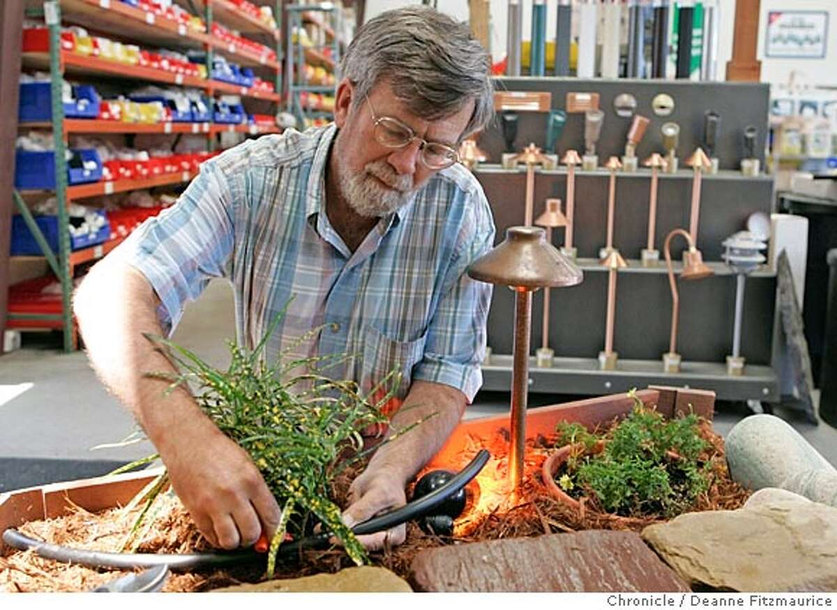 Tom Bressan, co-founder of Urban Farmer in Richmond, installs a drip irrigation system in the in-store display. San Francisco Chronicle/ Deanne Fitzmaurice