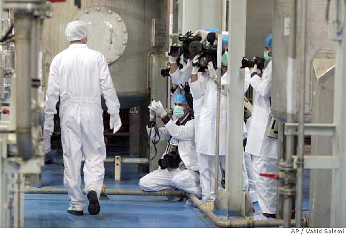 Cameramen and photographers take pictures as an Iranian technician walks through the Uranium Conversion Facility just outside the city of Isfahan 255 miles (410 kilometers) south of the capital Tehran, Iran, Saturday, Feb. 3, 2007. Diplomats from the Nonaligned Movement, Arab League and Group of 77 toured the nuclear facility Saturday in Iran's latest show of determination to continue its nuclear activities. The visit to the facility in central Iran is the first tour by diplomats of an Iranian nuclear facility since the United Nations Security Council approved economic sanctions on Iran on Dec. 23 for failing to halt uranium enrichment. (AP Photo/Vahid Salemi)