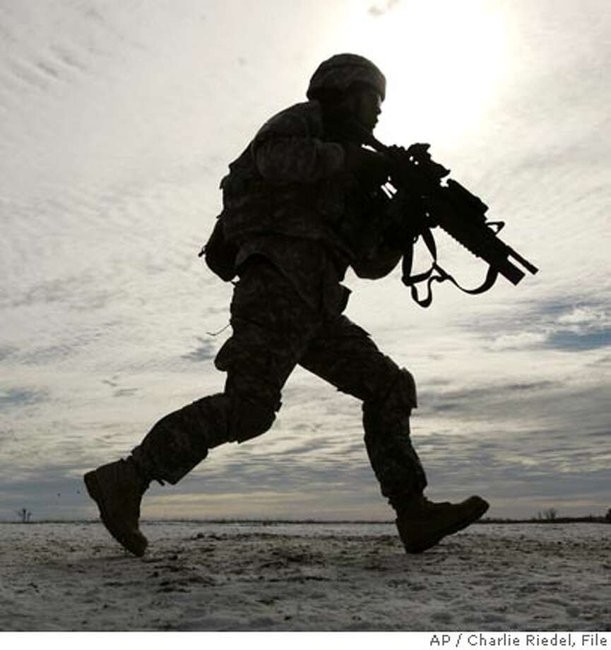 ** FILE ** Soldiers from the 1st Division, 4th Brigade run across a snow-covered prairie as they train at Fort Riley, Kan., in this Jan. 17, 2007, file photo as they prepare for deployment in Iraq. An internal Pentagon survey released Tuesday, Jan. 30, 2007, shows hundreds of U.S. troops in Iraq and Afghanistan have experienced shortages of key protective equipment including armored vehicles, roadside-bomb countermeasures, and communications gear. The Defense Department Inspector General's Office polled roughly 1,100 service members, and found they weren't always adequately equipped for their missions. The troops were interviewed in Iraq and Afghanistan last May and June. (AP Photo/Charlie Riedel, File) Photo: CHARLIE RIEDEL
