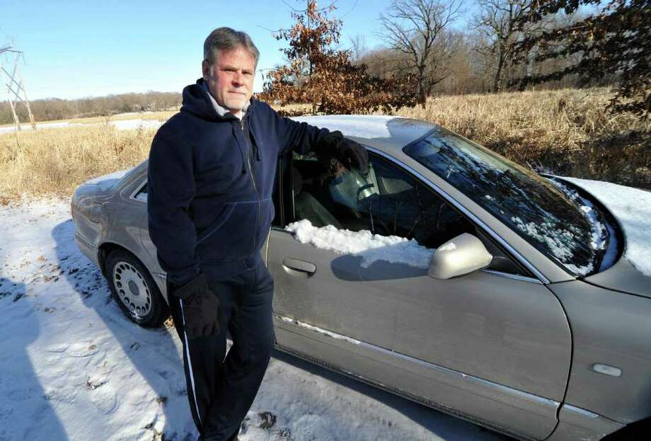 """Chris Jenks, 54, who became homeless in his hometown of Minneapolis-St. Paul after a successful career in sales and marketing, is shown outside a friends' home beside the car he lived in for a time on Thursday, Jan. 19, 2012, in Rogers, Minn. Though refusing to apply for for food stamps for several years, Jenks began receiving aid. """"I'm on food stamps because it's either that or I die,"""" he said. Photo: AP"""