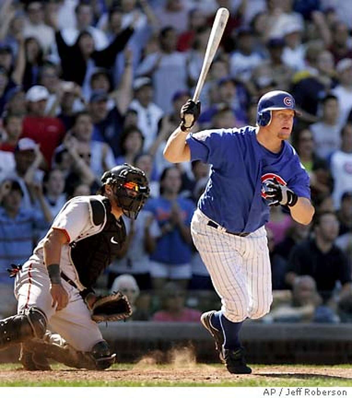 Chicago Cubs' Jeromy Burnitz, right, watches along with San Francisco Giants catcher Yorvit Torrealba, left, as his game-winning RBI single lands in the outfield during the bottom of the ninth Wednesday, July 27, 2005 in Chicago. The single scored the Cubs' Jody Gerut from second giving the Cubs a 4-3 victory. (AP Photo/Jeff Roberson)