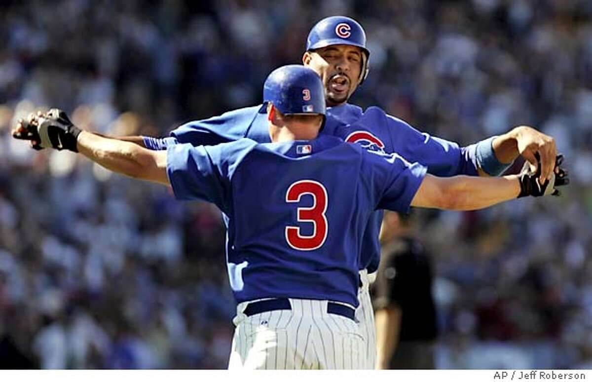 Chicago Cubs' Jeromy Burnitz (3) and Derrek Lee celebrate after Burnitz hit an RBI single in the bottom of the ninth to defeat the San Francisco Giants 4-3 Wednesday, July 27, 2005 in Chicago. (AP Photo/Jeff Roberson)