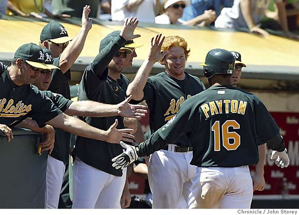 Jay Payton of the A's gets high fives after scoring the tying run in the 9th inning. The Oakland A's beat the Cleveland Indians in 10 innings at the McAfee Coliseum. John Storey Oakland Event on 7/27/05 -