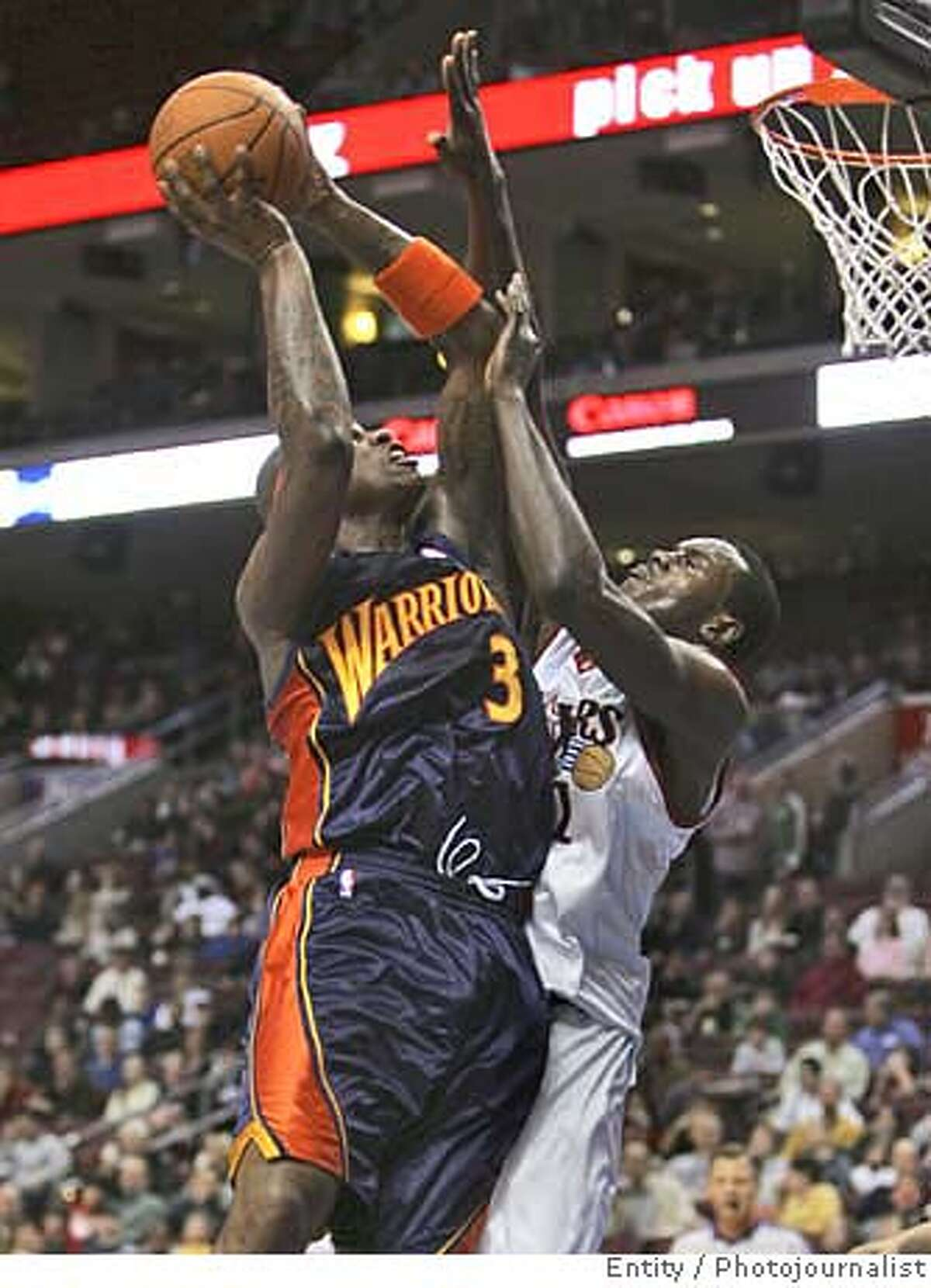 Golden State Warriors' Al Harrington (3) shoots over Philadelphia 76ers' Samuel Dalembert, of Haiti, during the first half of an NBA basketball game Friday, Feb. 2, 2007, in Philadelphia. (AP Photo/Rusty Kennedy) EFE OUT