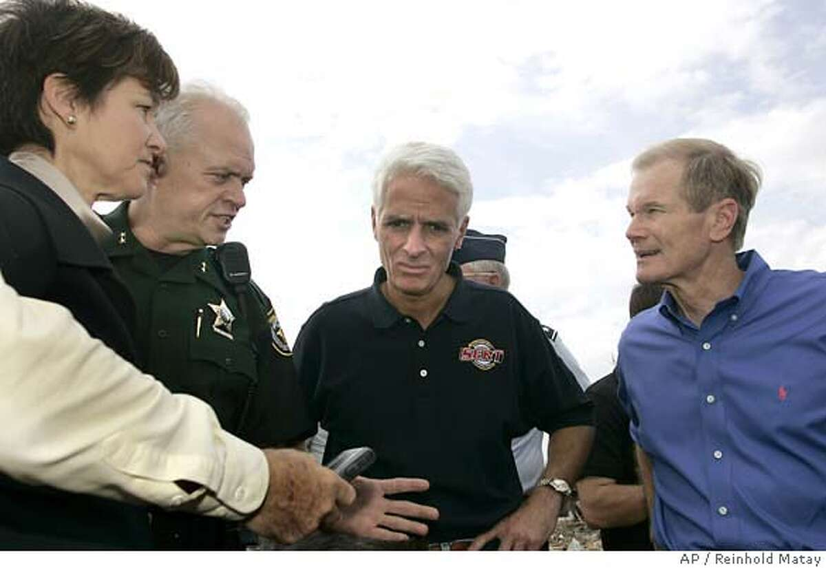 (Left to right) Florida Chief Financial Officer Alex Sink, Lake County Sheriff Gary Borders, Florida Gov. Charlie Crist and State Sen. Bill Nelson talk after early morning storms blew through the Bear Lake Blvd. section of Lake County, Fla., killing 11 people on Friday, Feb. 2, 2007. (AP Photo/Reinhold Matay)