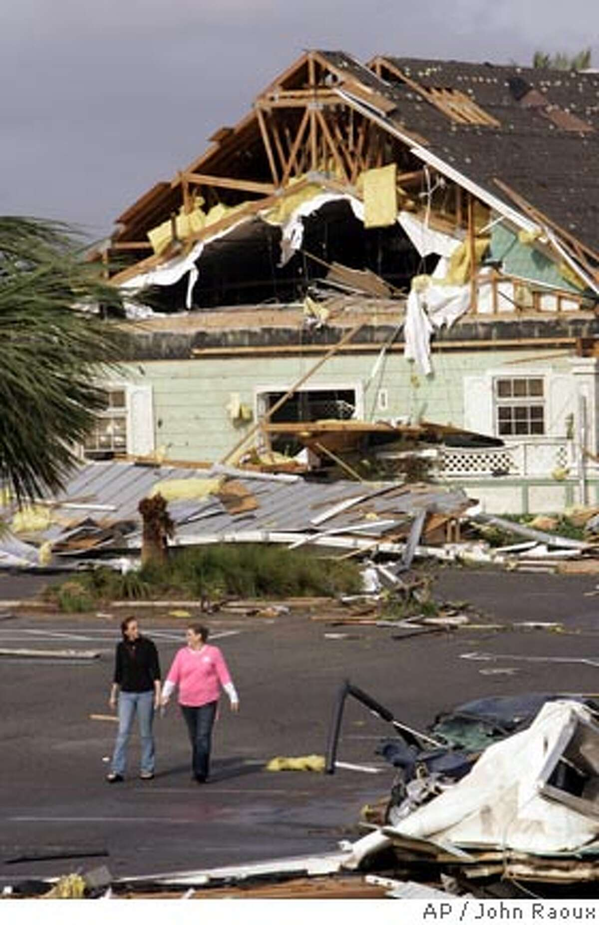 People walk through a residential neighborhood after damage from a tornado that hit early in the morning in The Villages, Fla., Friday Feb. 2, 2007. Storms blew through central Florida early Friday, killing at least 14 people, flattening dozens of homes and a church and lifting a tractor trailer into the air, authorities said. (AP Photo/John Raoux)