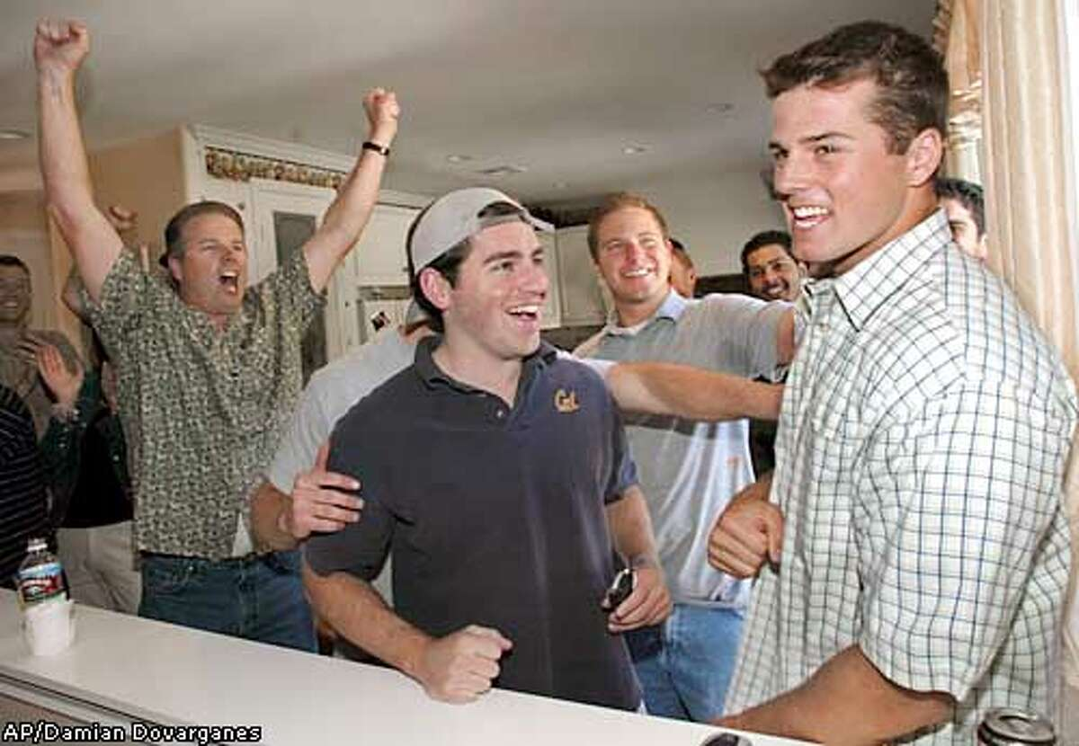 California quarterback Kyle Boller, far right, reacts as he learns that he is been drafted by the Baltimore Ravens Saturday, April 26, 2003, at his family home in Stevenson Ranch, Calif. Far left, with both hands up is Kyle's father Bob Boller. Chad Heydorff, second from left, among other former Cal State players in the background cheer up. (AP Photo/Damian Dovarganes)