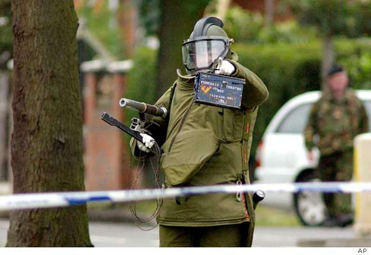 ** RETRANSMISSION TO REMOVE PIXELIZATION ** A Royal Logistic Corps bomb disposal expert approaches a house in Birmingham, England, Wednesday July 27, 2005, where detectives investigating the failed bomb attacks in London on July 21, made an arrest under the Terrorism Act 2000. Three men were arrested at another address in the city. (AP Photo/pa) ** UNITED KINGDOM OUT: : **