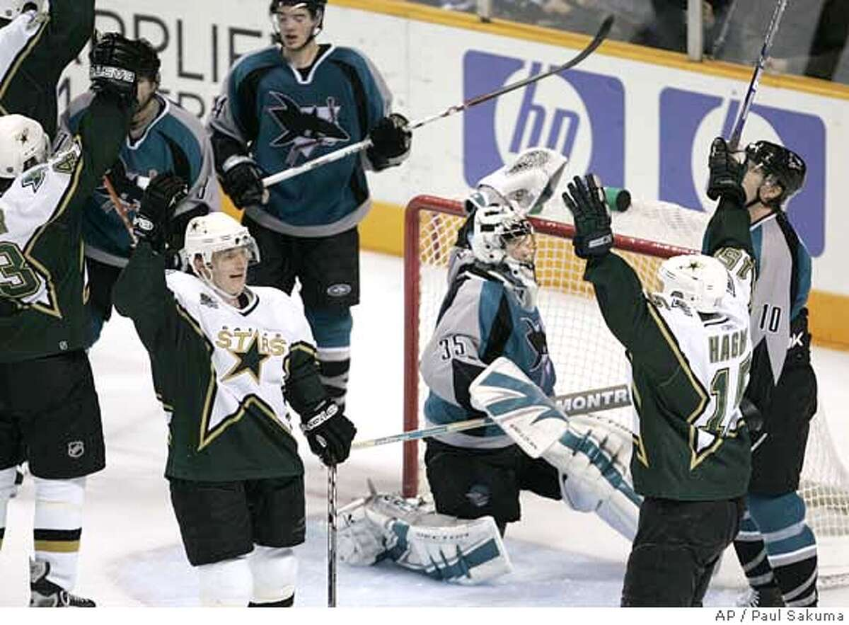 Dallas Stars right wing Jere Lehtinen, left, of Finland, and Stars left wing Niklas Hagman, right, also of Finland, celebrate in front of San Jose Sharks goalie Vesa Toskala, center, also of Finland, after Stars defenseman Philippe Boucher, left, scored in the closing seconds, to tie the NHL hockey game 2-2, in San Jose, Calif., Tuesday, Jan. 30, 2007. The Stars won in a shootout 3-2. (AP Photo/Paul Sakuma) EFE OUT