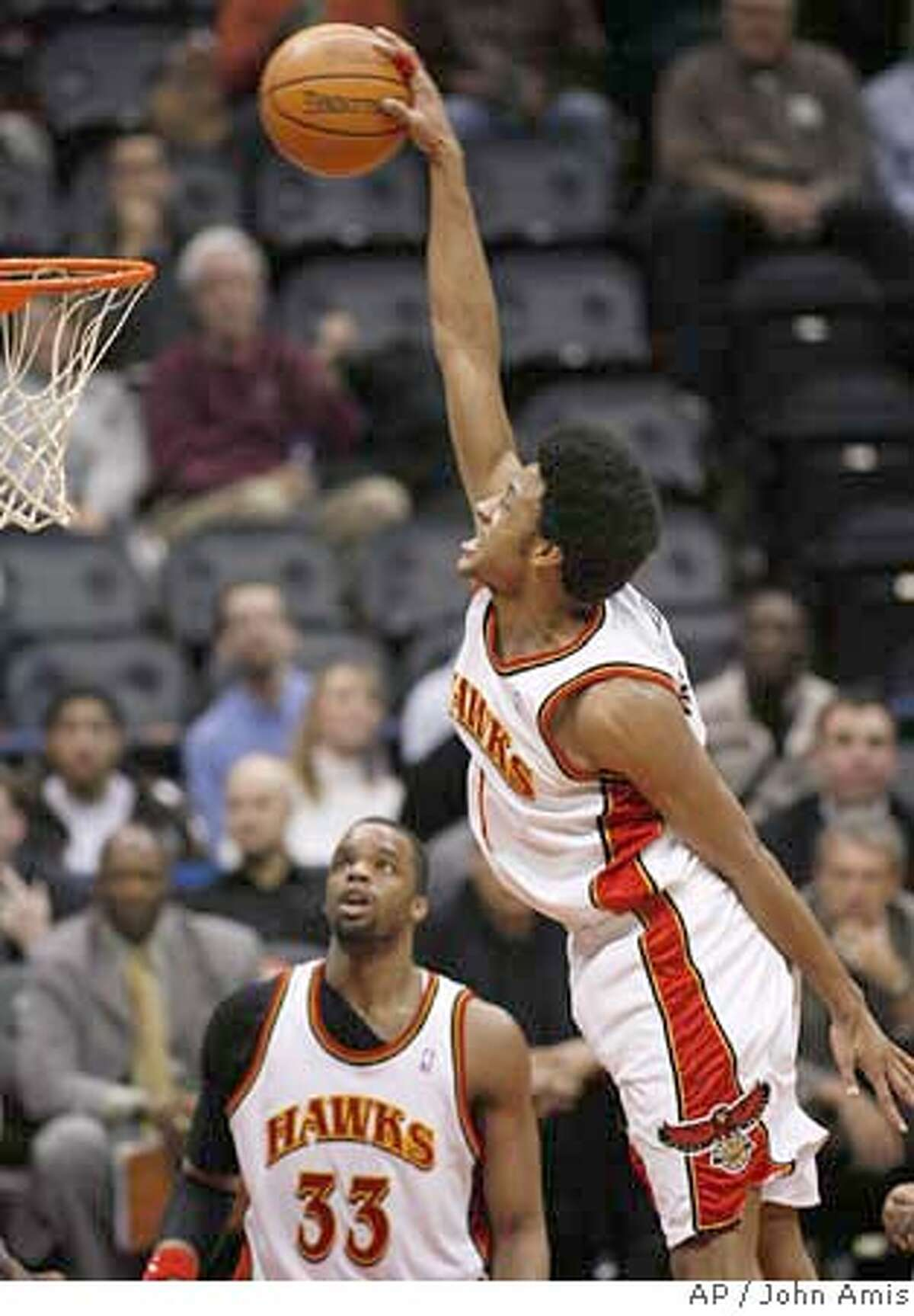 Atlanta Hawks' Josh Childress goes high above the basket before dunking, as forward Shelden Williams (33) looks on during the second half of an NBA basketball game against the Golden State Warriors on Wednesday, Jan. 31, 2007, in Atlanta. (AP Photo/John Amis) EFE OUT