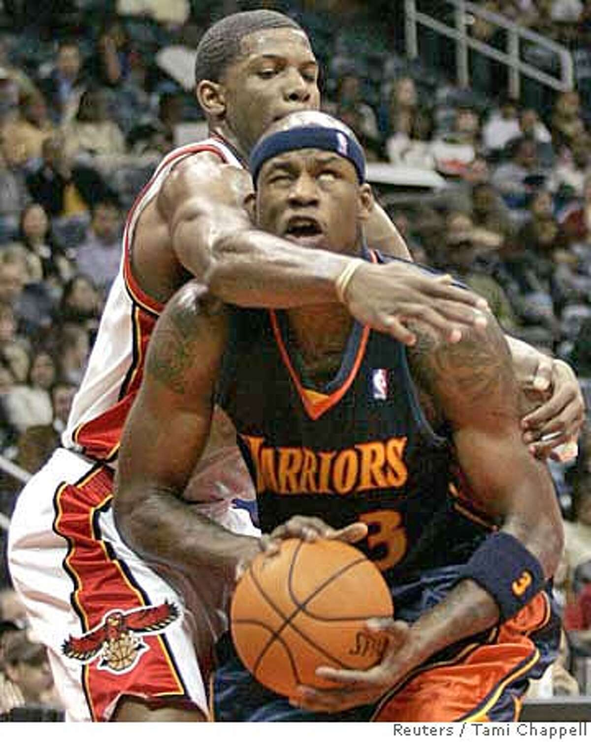 Golden State Warriors forward Al Harrington is fouled under the basket by Atlanta Hawks guard Joe Johnson (rear) in the first half of their NBA basketball game in Atlanta, Georgia January 31, 2007. REUTERS/Tami Chappell (UNITED STATES)