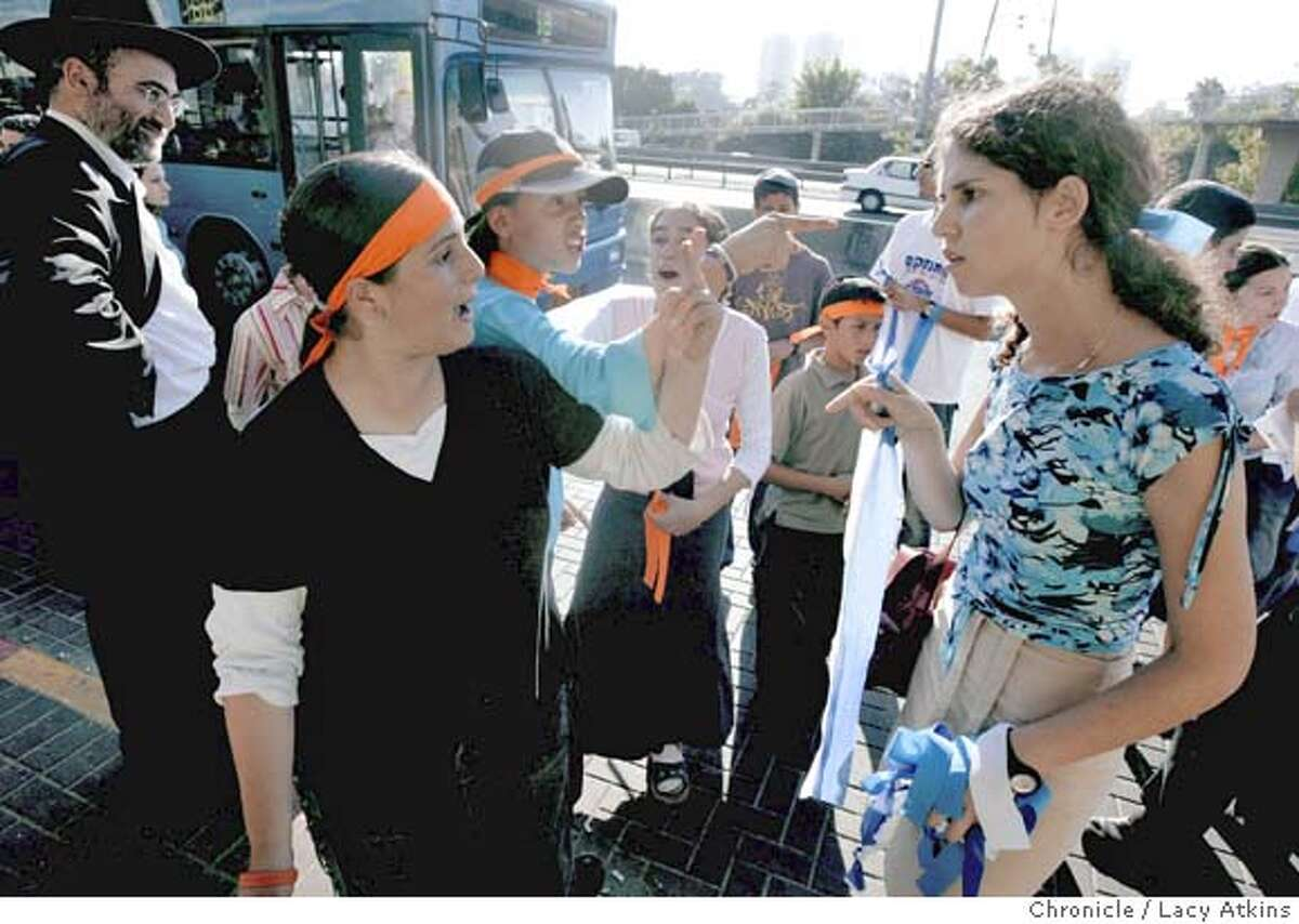 Left to right--- Anti disengagement protesters who wear orange ribbons Cheh Mehashe and Yael Auhar argue their views with Michal Goral who is in favor of the disengagement and wears blue ribbons, during the country wide ribbon war, June 29, 2005, throughout Israel.Photographer Lacy Atkins