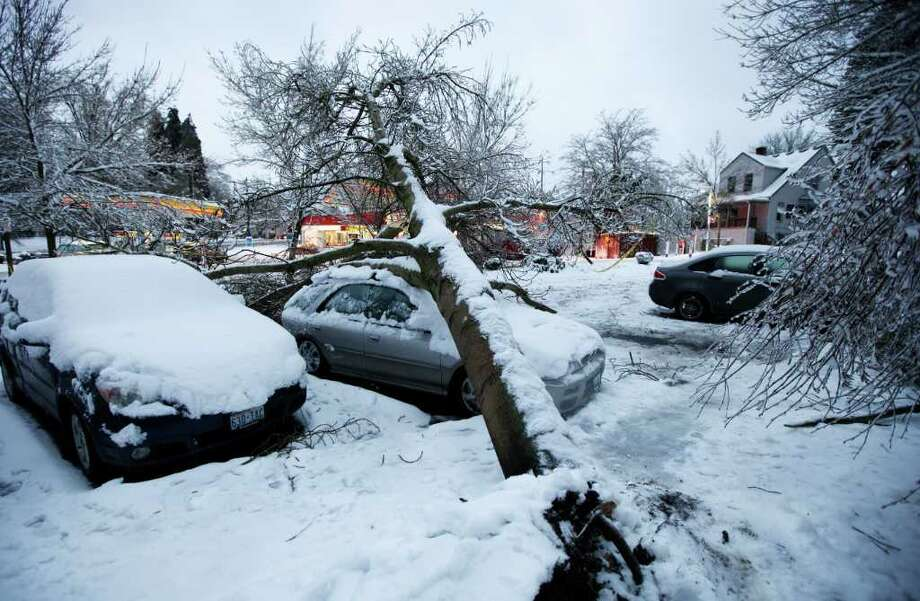 A tree rests on a car, Thursday, Jan. 19, 2012, in Tacoma, Wash. On the heels of heavy snow that fell Wednesday, the Western Washington region was hit with an ice storm Thursday that coated trees and vehicles with a heavy coat of ice. (AP Photo/Ted S. Warren) Photo: Ted S. Warren / AP