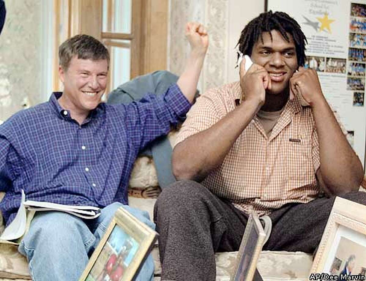 Kwame Harris, right, an offensive tackle from Stanford, is notified he was selected by the San Francisco 49ers in the NFL draft as his agent, Leigh Steinberg, sits next to him Saturday, April 26, 2003, in Newark, Del. (AP Photo/The News Journal, Dee Marvin)