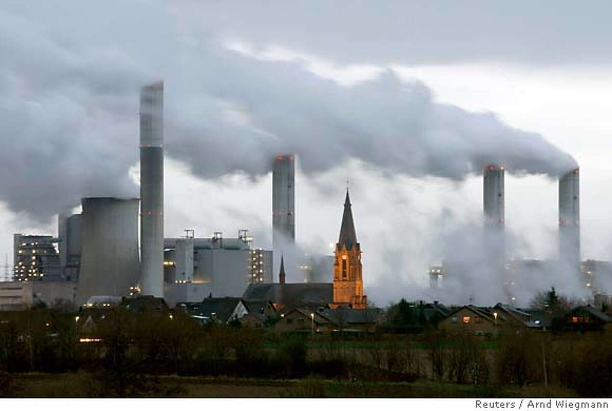 The village of Gusdorf, west of Cologne, is pictured in front of the lignite-fired power plant Frimmersdorf of German RWE AG energy company in this December 3, 2006 file photo. The Intergovernmental Panel on Climate Change (IPCC) February 2, 2007, released its long-awaited report assessing the human link to pollution, global warming and climate change. REUTERS/Arnd Wiegmann/Files (GERMANY)