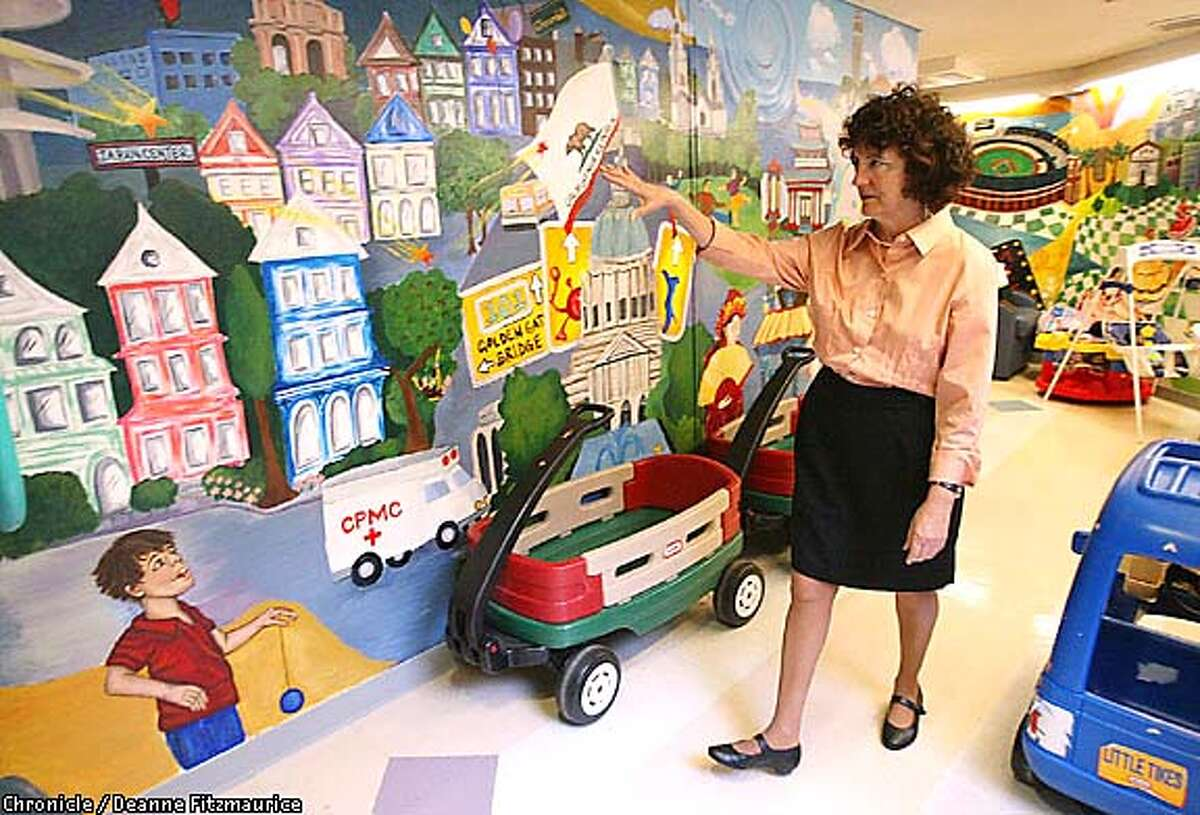 Joanna Fanos walks past a mural in the pediatric center at California Pacific Medical Center, where she founded the Sibling Center to help children with sick siblings. Chronicle photo by Deanne Fitzmaurice