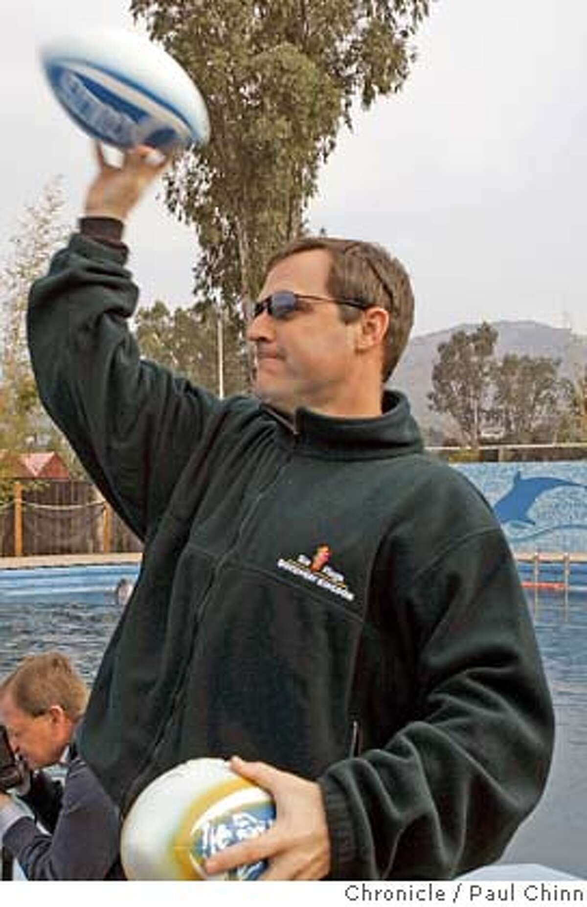 Kirk Smith, a former quarterback at the College of Marin, tosses the footballs into the pool. Merlin, a prognosticating dolphin, has predicted a Super Bowl victory by the Indianapolis Colts after making his selection in his pool at Six Flags Discovery Kingdom amusement park in Vallejo, Calif. on Wednesday, Jan. 31, 2007. Two footballs - one bearing the name of the Colts, the other with the Chicago Bears - were thrown into the pool for him to pick. According to park officials, Merlin has a 75% accuracy rate. PAUL CHINN/The Chronicle **Kirk Smith