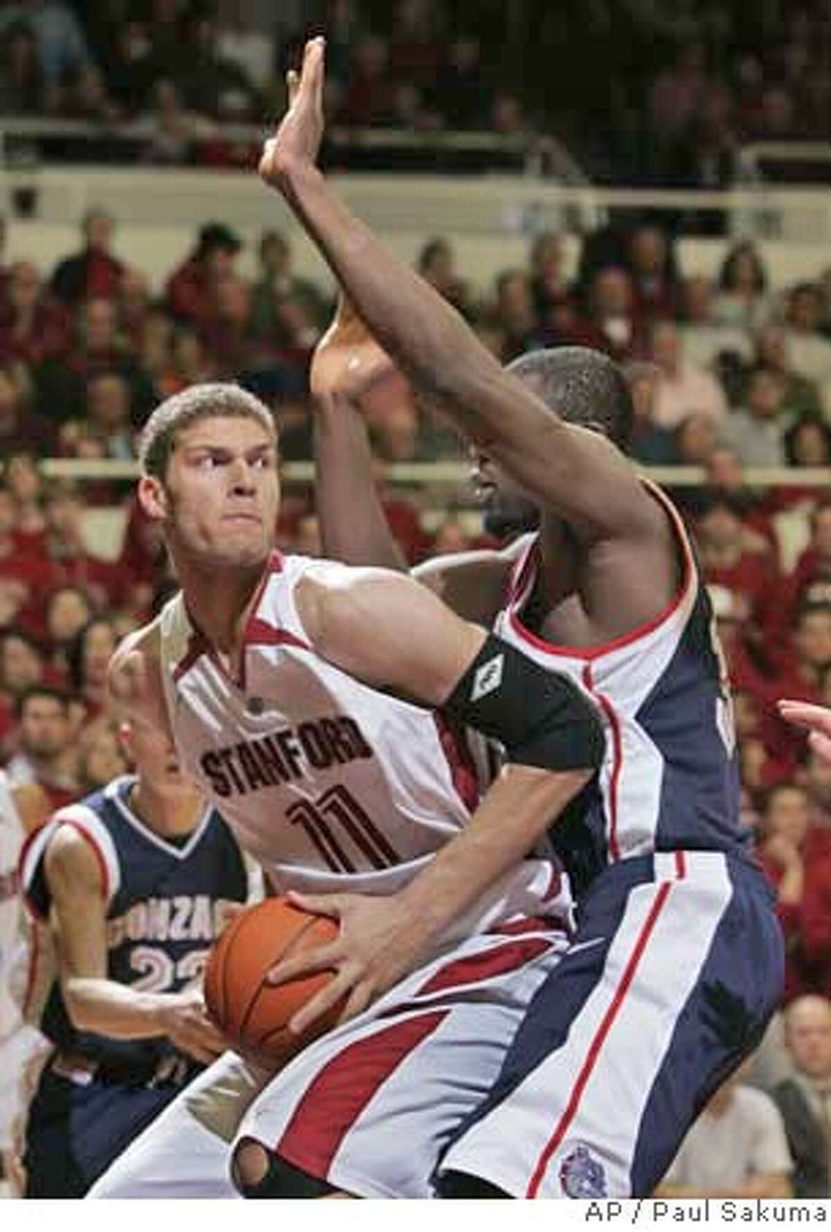 Stanford forward Brook Lopez, left, is closely guarded by Gonzaga forward Abdullahi Kuso during the second half of a basketball game in Stanford, Calif., Wednesday, Jan. 31, 2007. (AP Photo/Paul Sakuma)