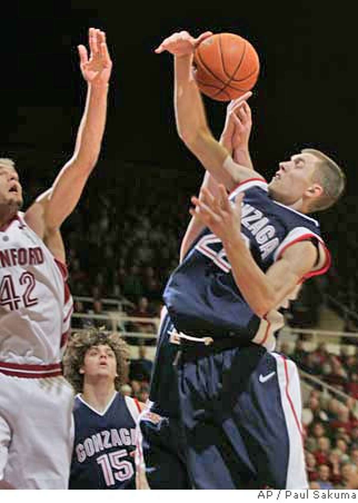 Gonzaga guard Micah Downs (22) and Stanford center Robin Lopez, (42) go for rebound in the first half of their NCAA basketball game in Stanford, Calif., Wednesday, Jan. 31, 2007. (AP Photo/Paul Sakuma)