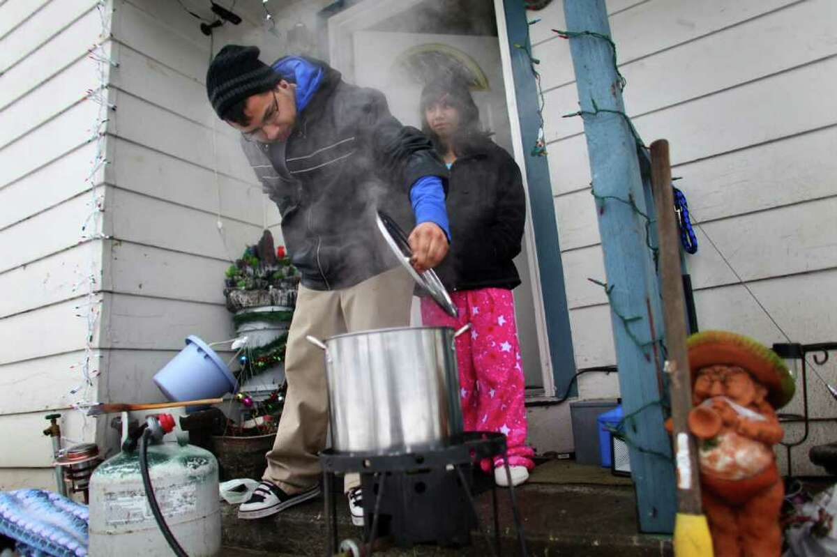 Jaime Rodriguez checks on his dinner as his sister Krystal Rodriguez, 13, keeps watch from their front porch on Friday, January 20, 2012 in Auburn. An ice storm wreaked havoc in the area, bringing down trees and power lines. Power was out in large parts of the area.