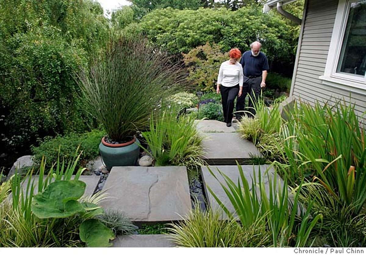 Paul and Robin Cowley walk up the stone path at the top of the garden. The Potomac Waterworks backyard garden at the home of landscape architect Paul Cowley and his wife Robin on 6/24/05 in Oakland, Calif. The garden features fountains, a pond and two streams. PAUL CHINN/The Chronicle