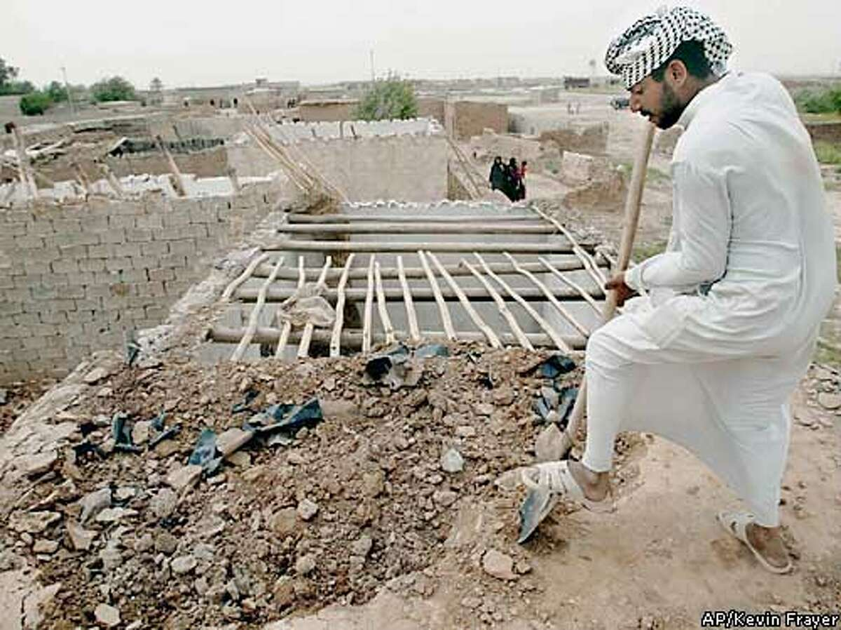 An Iraqi Shiite man destroys the roof of his home before moving, in Al Nasser, north of Kirkuk, Iraq Friday April 25, 2003. The Shiite families, who moved to the village as part of Saddam Hussein's program to move Arabs to northern Iraq, are being forcibly evicted by Kurds who have returned to reclaim the land. (AP Photo/Kevin Frayer)