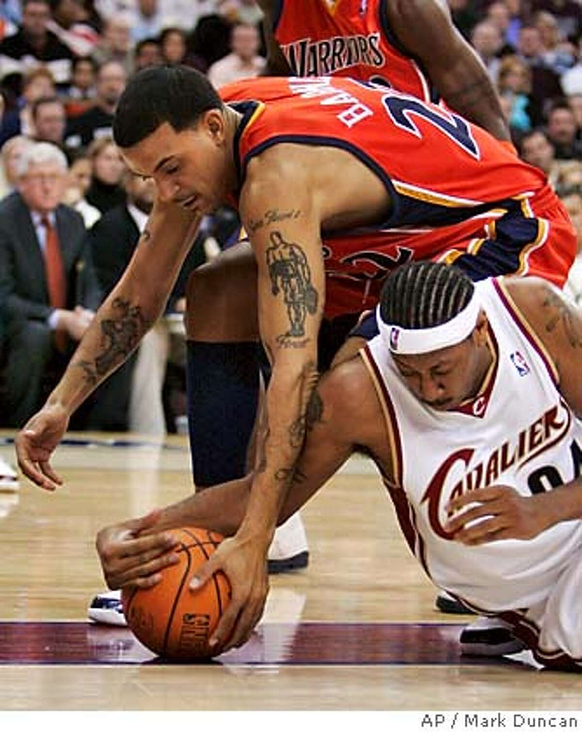 Golden State Warriors' Matt Barnes, top, fights for a loose ball with Cleveland Cavaliers' Donyell Marshall during the second quarter of an NBA basketball game Tuesday, Jan. 30, 2007, in Cleveland. (AP Photo/Mark Duncan)