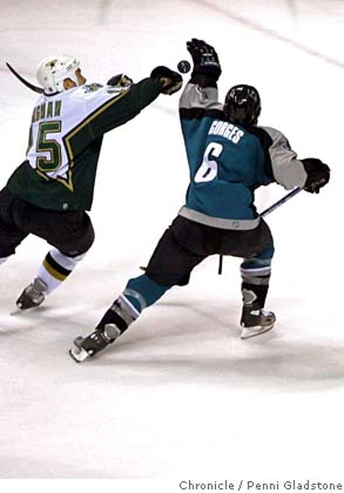 San Jose Sharks vs Dallas Stars In the 2nd period it's hand hockey...as Stars Niklas Hagman reaches for the puck with Sharks Josh Gorges. Event on 1/30/07 in San Jose. Penni Gladstone / The Chronicle