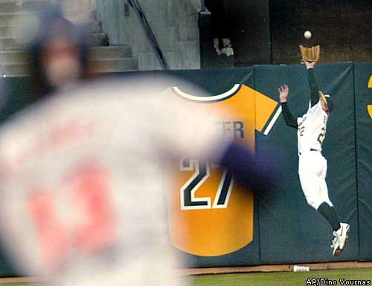 Oakland Athletics left fielder Eric Byrnes robs Cleveland Indians batter Omar Vizquel (out of focus in foreground) of extra bases during the third inning Friday, April 25, 2003, in Oakland, Calif. (AP Photo/Dino Vournas)