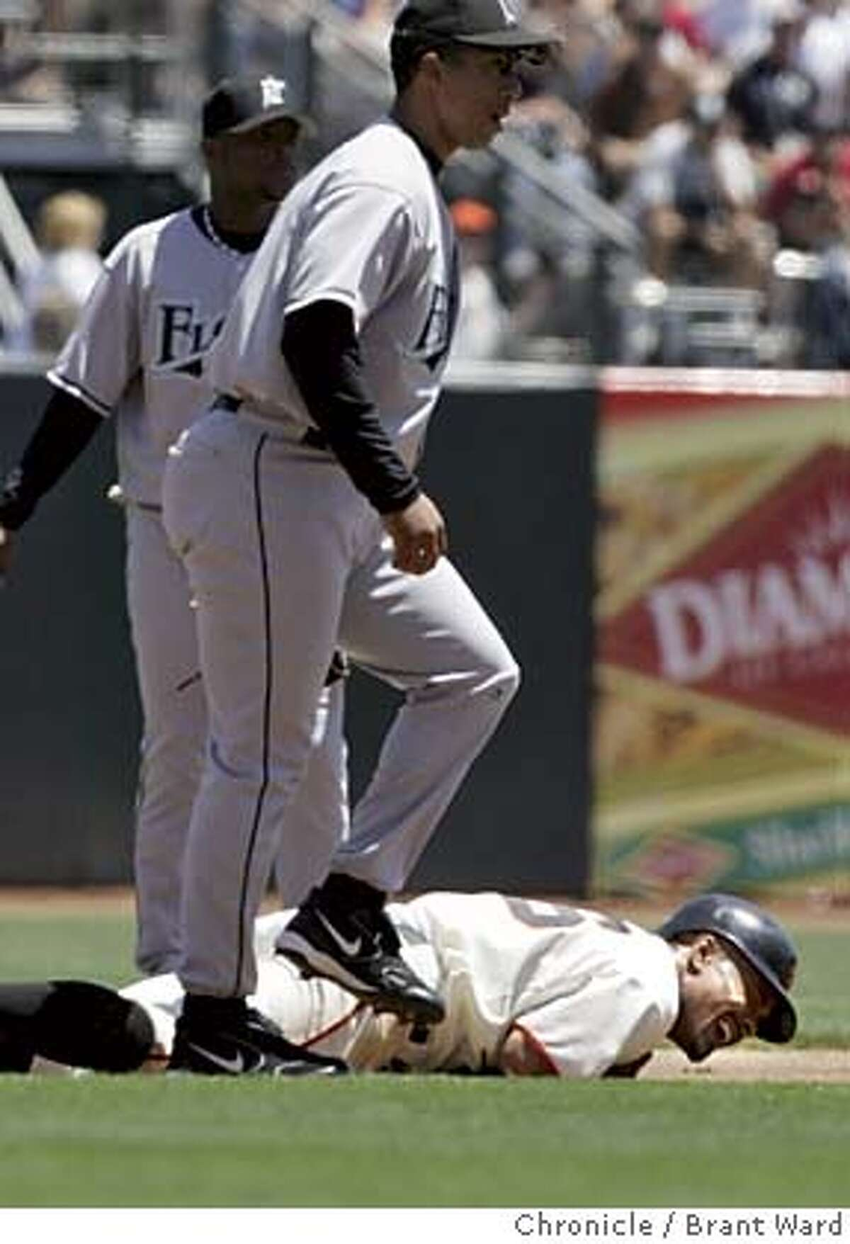 The Giants were undone on the bases...here Jason Ellison is in pain after being forced at second in the first inning on a fielders choice by Edgardo Alfronso. Damion Easley defends. The Giants finished their home stand with a loss against the Marlin's 4-1 at SBC Park.Brant Ward 7/25/05