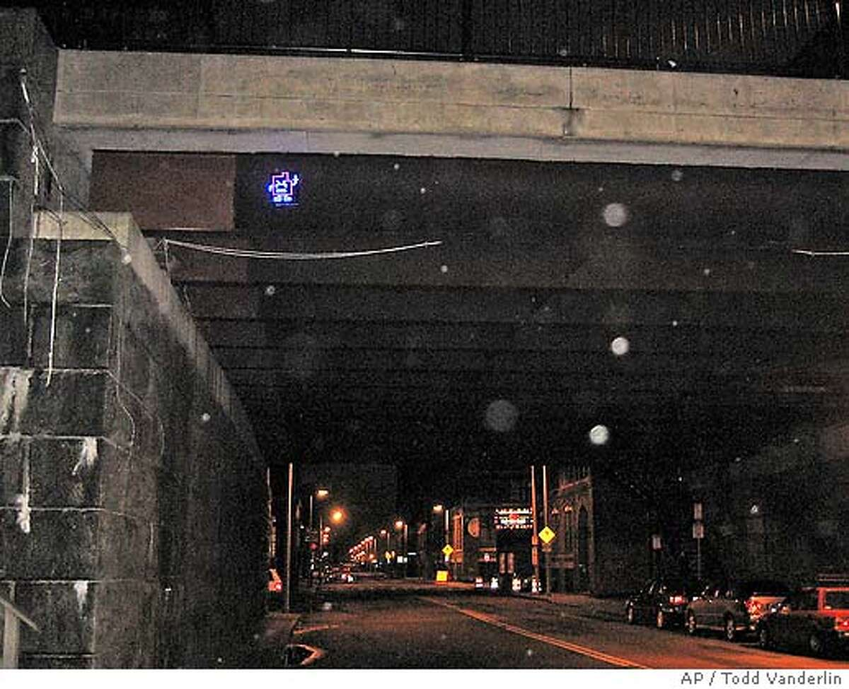 This photo provided by Todd Vanderlin shows an electronic device hanging beneath an overpass in Boston, Monday Jan. 15, 2007. The device consists of light emitting diodes on a circuit board forming the shape of a gesturing character which is part of a promotion for the TV show