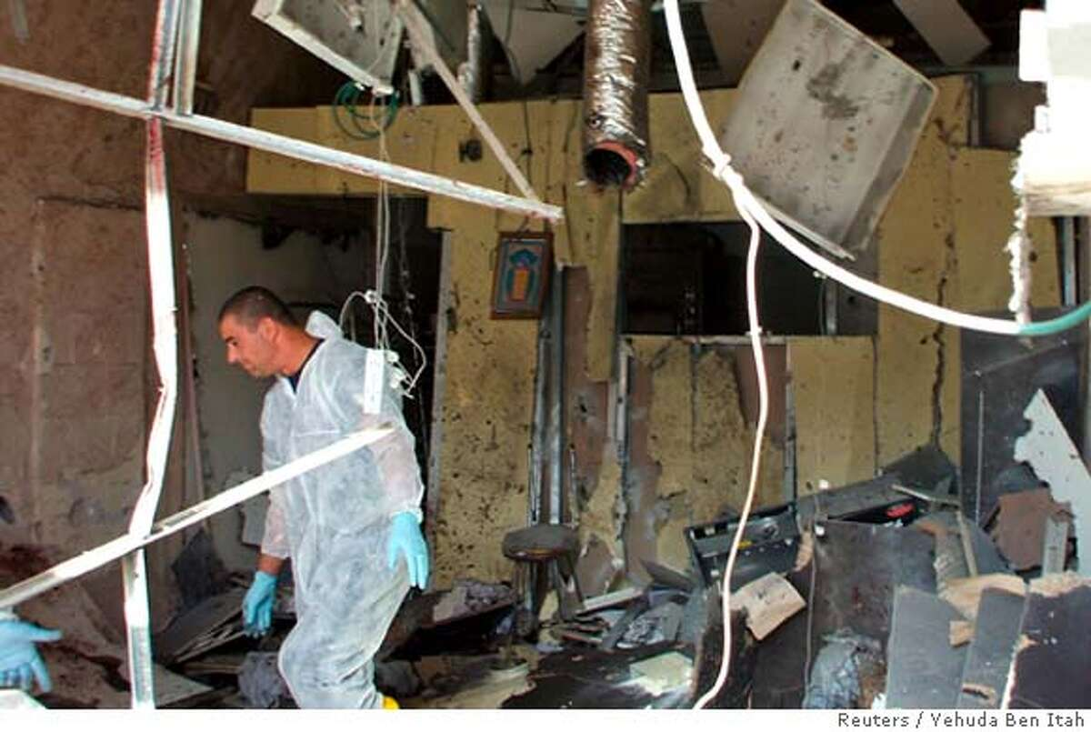 An Israeli policeman surveys the scene of an explosion in the southern city of Eilat January 29, 2007. A Palestinian suicide bomber killed three people in a bakery in the Red Sea resort of Eilat, one of Israel's most popular holiday spots, in the first such attack in the Jewish state in nine months, police said. ISRAEL OUT FOR EDITORIAL USE ONLY REUTERS/Yehuda Ben Itah (ISRAEL)