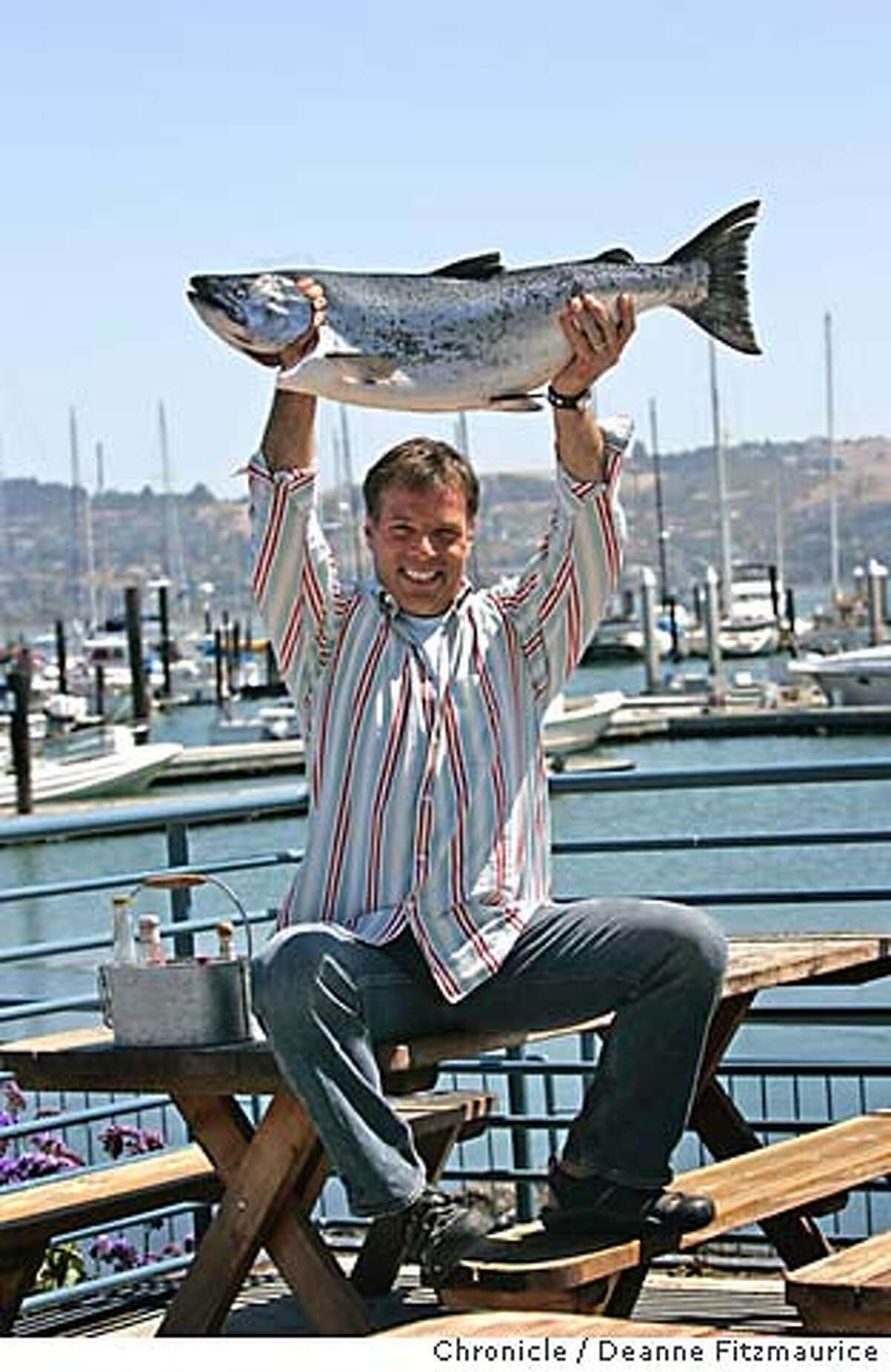 TV Chef, Joey Altman holds a freshly caught local salmon on a picnic bench at a restaurant he likes, Fish restaurant in Sausalito. San Francisco Chronicle/ Deanne Fitzmaurice