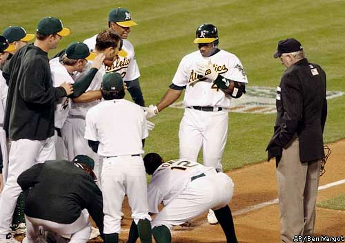 Oakland Athletics welcome Miguel Tejada, second from right, at home plate after Tejada hit a game-winning home run off Detroit Tigers' Wilfredo Ledezma in the 11th inning Tuesday, April 22, 2003, in Oakland, Calif. The Athletics won 6-5. (AP Photo/Ben Margot)