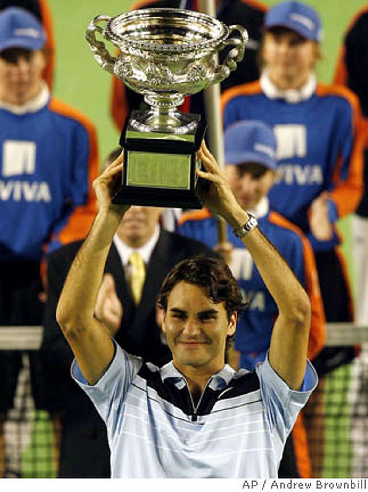 Switzerland's Roger Federer holds his trophy after winning the men's singles final against Chile's Fernando Gonzalez at the Australian Open tennis tournament in Melbourne, Australia, Sunday, Jan. 28, 2007. Federer won in straight sets 7-6 6-4 6-4. (AP Photo/Andrew Brownbill)