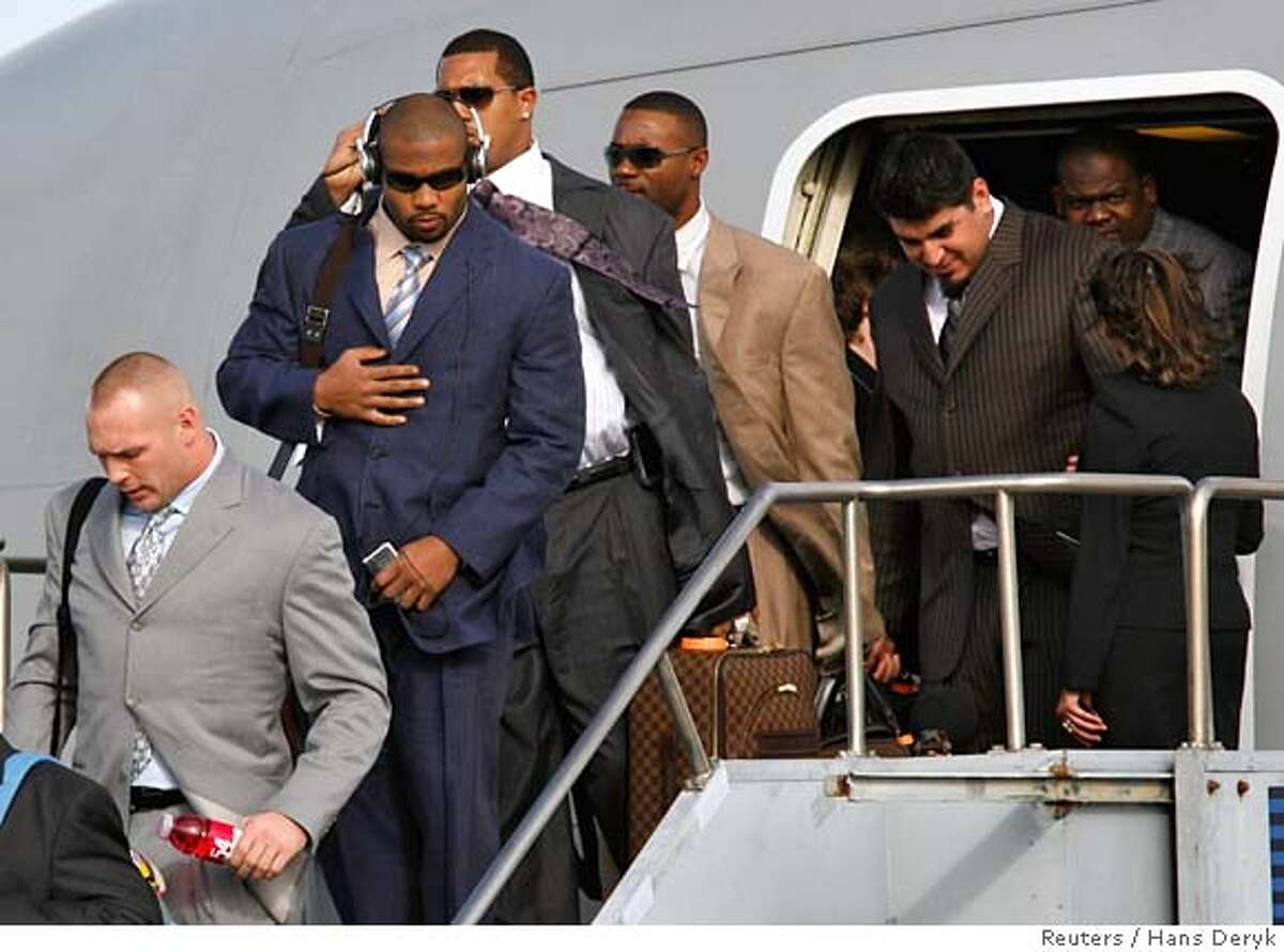 Brian Urlacher (L) and Lance Briggs lead players of the Chicago Bears off the team charter after arriving at Miami International Airport January 28, 2007. The Bears with play the Indianapolis Colts in Super Bowl XLI. REUTERS/Hans Deryk (UNITED STATES)