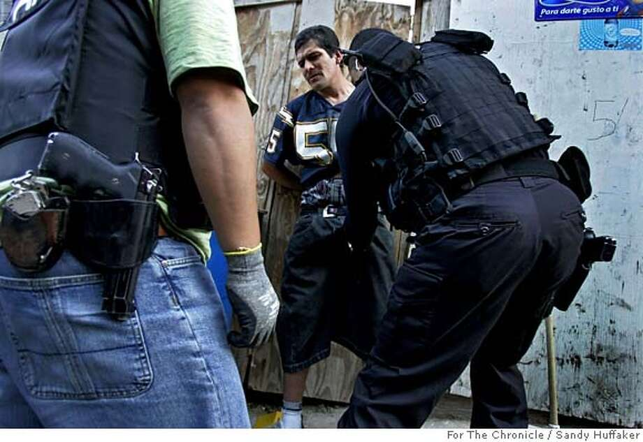 Tijuana Police agents search a man for illegal contraband during a drug sweep in Colonia Chula Vista on Thursday, December 14, 2006 in Tijuana, Mexico.(Photo by Sandy Huffaker for the SF Chronicle) Photo: Sandy Huffaker