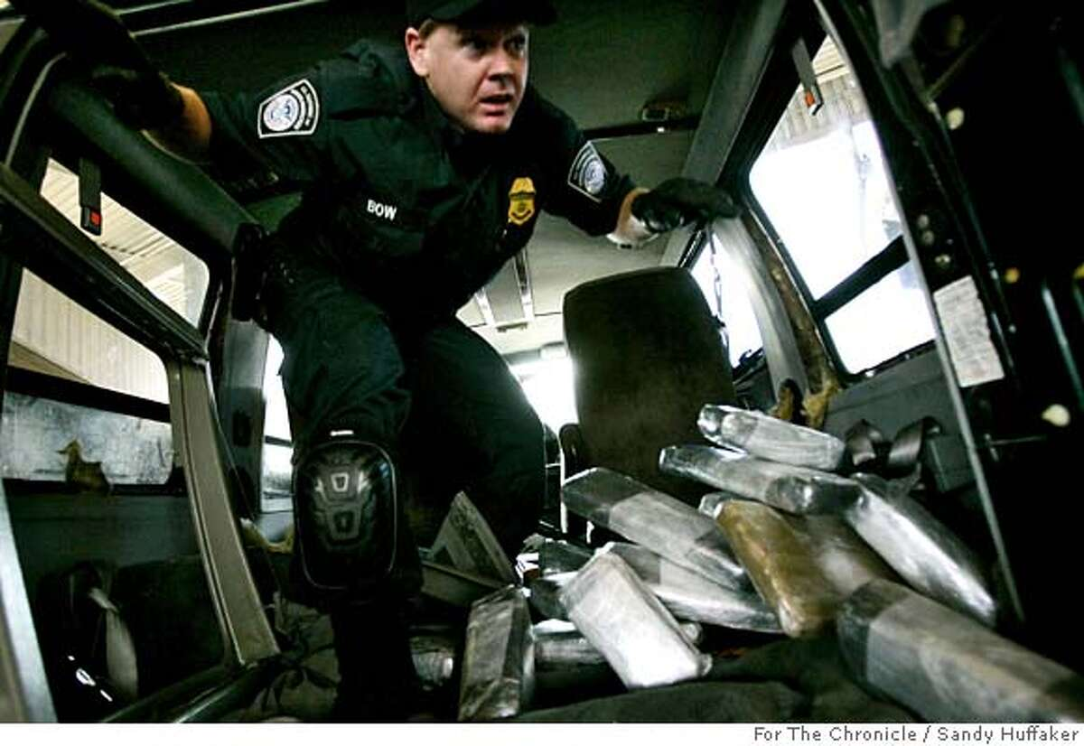 Customs and Border Protection agent Ian Bow exits a van after pulling out bricks of Marijuana at the U.S. Port of Entry in San Ysidro, Calif. on Friday, December 15, 2006. The drugs were concealed throughout the van behind wall paneling and in a chamber in the gas tank.(Photo by Sandy Huffaker for the SF Chronicle)