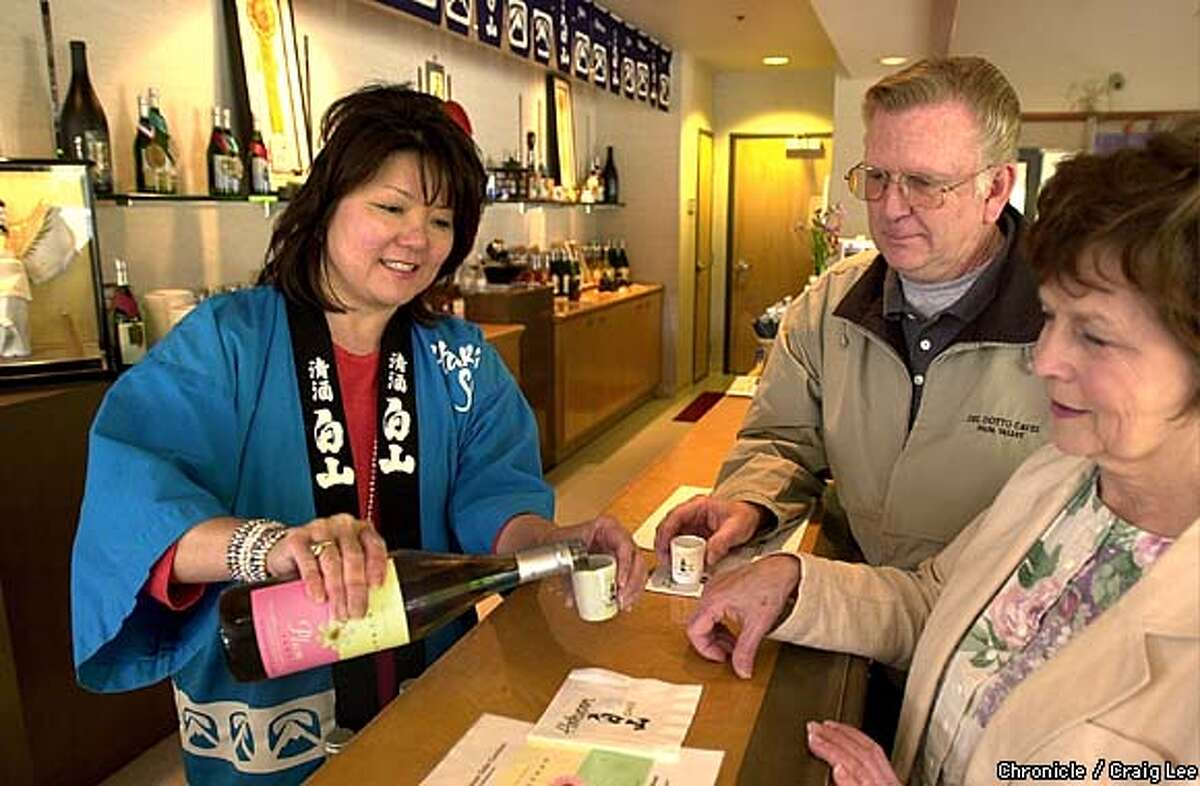 Hakusan Sake Gardens, One Executive Way, Napa, CA. Photo of Hideko Pond, tasting room manager, pouring some sake for Larry and Joan Brady of Sonoma. Photo by Craig Lee/San Francisco Chronicle