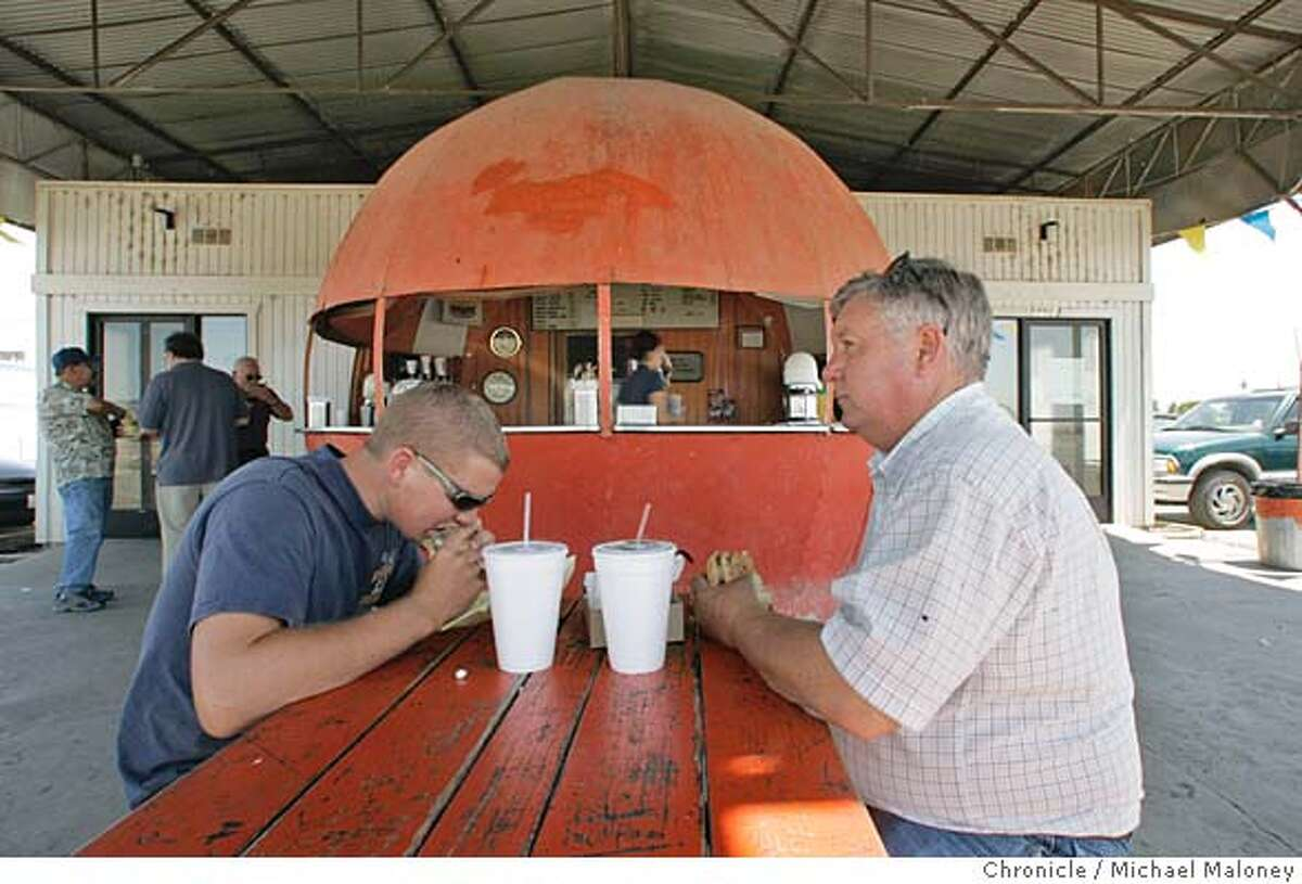 Taking a lunch break at the Mammoth Orange Drive-In are William (left) and David Pruitt of Dos Palos. The father and son were heading down Highway 99 to shop for a truck and stopped at the drive-in for burgers. Alongside Highway 99 just north of Madera is the Mammoth Orange Drive-In, a large orange ball offering shade, orange juice and