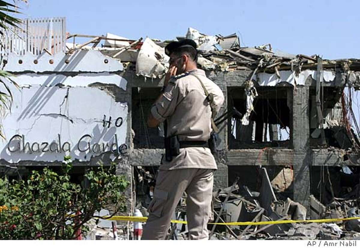 An Egyptian policeman stands in front of the damaged Ghazala Gardens Hotel following explosions in Egypt's Red Sea resort of Sharm el-Sheik early Saturday July 23, 2005. Explosions ripped through a luxury hotel and a coffee shop in the Red Sea resort of Sharm el-Sheik early Saturday, killing at least 75 people. Terrified European and Arab tourists fled into the night, but the toll hit heaviest on Egyptian workers. (AP Photo/Amr Nabil)
