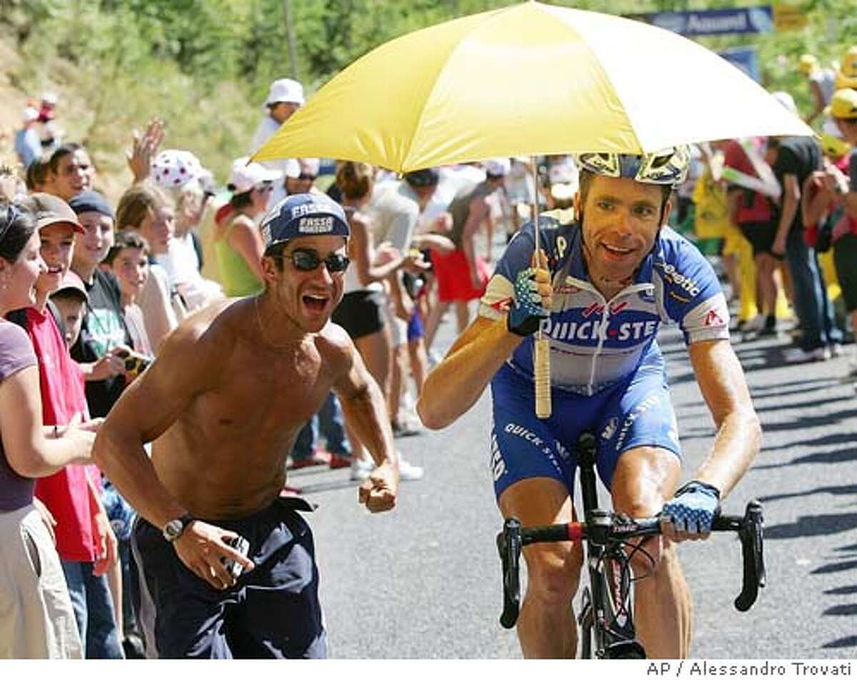 Bram Tankink of The Netherlands rides up the Croix-Neuve pass with an umbrella he picked up from a spectator during the 18th stage of the Tour de France cycling race between Albi, southwestern France, and Mende, southern France, Thursday, July 21, 2005. (AP Photo/Alessandro Trovati)