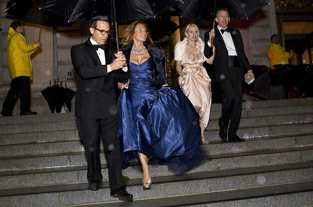 Alan Malouf (left) helps Elisabeth Thieriot keep dry while walking from dinner to the performance during the San Francisco Ballet Opening Night Gala at City Hall in San Francisco, Calif., on Thursday, January 19, 2012. Photo: Laura Morton, Special To The Chronicle