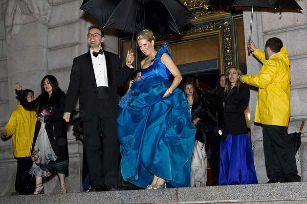 Andrew Trader helps gala chairwoman Marie Hurabiell keep dry while walking from dinner to the performance during the San Francisco Ballet Opening Night Gala at City Hall in San Francisco, Calif., on Thursday, January 19, 2012. Photo: Laura Morton, Special To The Chronicle